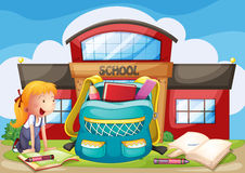 A girl with her school supplies in front of the school building Stock Photography