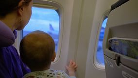 The girl and her son look out the window of the plane in slow motion. The girl and her small cute son look out the window of the plane before takeoff. Action in stock footage
