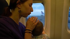 The girl and her small son look out the window of the plane in slow motion. The girl and her small cute son look out the window of the plane before takeoff stock footage
