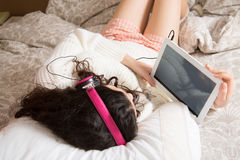 Girl with her tablet in bed Royalty Free Stock Images
