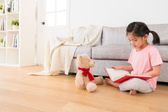 Girl and her teddy bear seriously study Royalty Free Stock Photos
