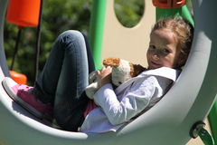 The girl with her toy. Smiling girl with her toy dog lies, portrait, Sunny day Royalty Free Stock Images