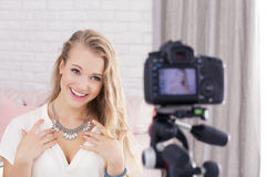 Girl and her video blog. Pretty girl recording on a camera her video blog Royalty Free Stock Photos