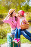 The girl and her younger sister in the nature near the river Stock Photos