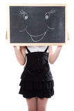 Girl hid behind a blackboard with the smile image Royalty Free Stock Photos