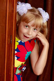 The girl hid behind the wardrobe. Cheerful little girl hiding behind an old wardrobe . retro style Royalty Free Stock Images