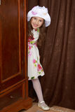 The girl hid behind the wardrobe. Cheerful little girl in a smart white dress with the roses peeping from behind the old Cabinet Royalty Free Stock Photo