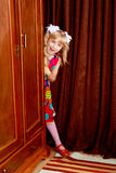 The girl hid behind the wardrobe. Cute little girl hidden behind an old wardrobe . retro style Royalty Free Stock Photos
