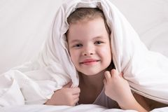 The girl hid her head under a white blanket, looked and smiled stock image