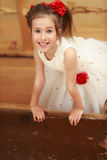 The girl hid in an old trunk. Cute little girl in a white dress hiding in the old chest, which smelled of mothballs. Girl looks out of it stock photography