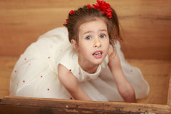 The girl hid in an old trunk. Cute little girl in a white dress hiding in the old chest, which smelled of mothballs. Girl looks out of it up royalty free stock photos