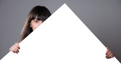 Girl hidden behind a white sheet of paper Stock Images