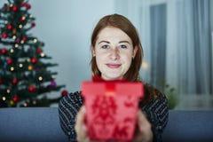 Girl hide behind christmas present box Stock Photography