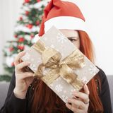 Girl is hide behind christmas present Stock Photography