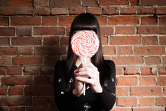 Girl hide her face with big lollipop a lot of copyspacve on red brick wall Royalty Free Stock Photography
