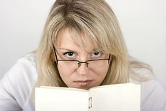 The girl hides behind the book Royalty Free Stock Photos