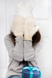 Girl hides behind fur mittens Stock Images