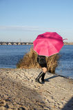 Girl hides behind an umbrella. Girl on the banks of the river is hidden from the wind for an umbrella Royalty Free Stock Image