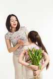 The girl hides a bouquet of flowers for mother Stock Image