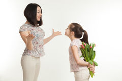 The girl hides a bouquet of flowers for mother Royalty Free Stock Image