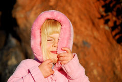 Girl hides face. Toddler girl (three years old) with blond hair, wearing pink jacket, hides her face from the sun royalty free stock photo