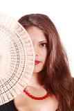 Girl hides half of her face by fan. Beautiful girl looks at camera and hides half of her face by fan isolated on white background Royalty Free Stock Images