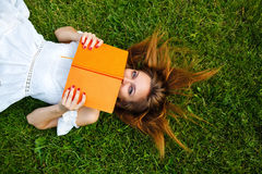 Girl hides her face behind book lying on lawn. Royalty Free Stock Photography