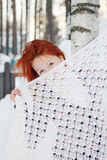 Girl hides her face behind shawl near birch at winter Royalty Free Stock Image