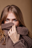 Girl hides her face in a warm sweater. We see only the eyes. Stock Images