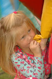Girl hiding. A beautiful little caucasian blond white girl child with cute expression in the pretty face hiding behind a jumping castle playing hide and seek on Royalty Free Stock Photography