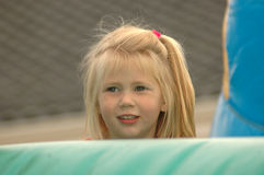 Girl hiding. A beautiful little girl child head portrait with long blond hair and smiling expression in the face hiding behind a jumping castle on the playground Stock Image