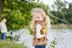 Girl hiding autumn leaf as a surprise stock image