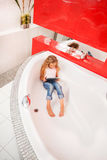 Girl hiding in the bathroom, playing in tablet Royalty Free Stock Photography