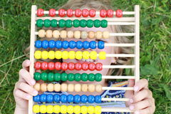 Girl hiding behind an abacus Stock Photography