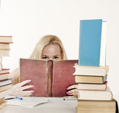Girl hiding behind the book,. Staring at you Stock Photo