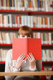 Girl hiding behind the book Royalty Free Stock Photography