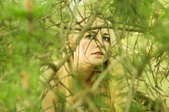 Girl hiding behind branches Stock Photo