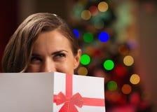 Girl hiding behind Christmas postcard. In room Stock Photos