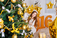 Girl hiding behind Christmas tree. New Year 2016. Stock Photos