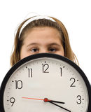 Girl Hiding Behind Clock. Young girl hiding behind a large wall clock, isolated against a white background Stock Photography