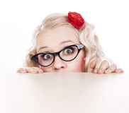 Girl hiding behind a desk Stock Image