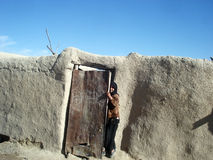 Girl hiding behind a door in Afghanistan stock image