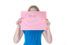 Girl hiding behind fake face. Girl hiding behind happy face royalty free stock images