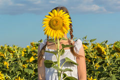 Girl hiding behind flower sunflower Royalty Free Stock Images