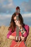 Girl hiding behind a guitar Stock Photo