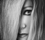 Girl Hiding Behind Hair in Face. A girl is hiding behind her straight hair in her face in a black and white photo. Her eye is peaking out and she is serious for Royalty Free Stock Photo