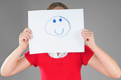 Girl hiding behind happy face Stock Image