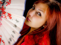 Girl hiding behind japaneese fan. Stock Photos