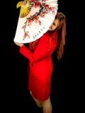 Girl hiding behind japaneese fan. Stock Photography