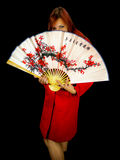 Girl hiding behind japaneese fan. Stock Photo